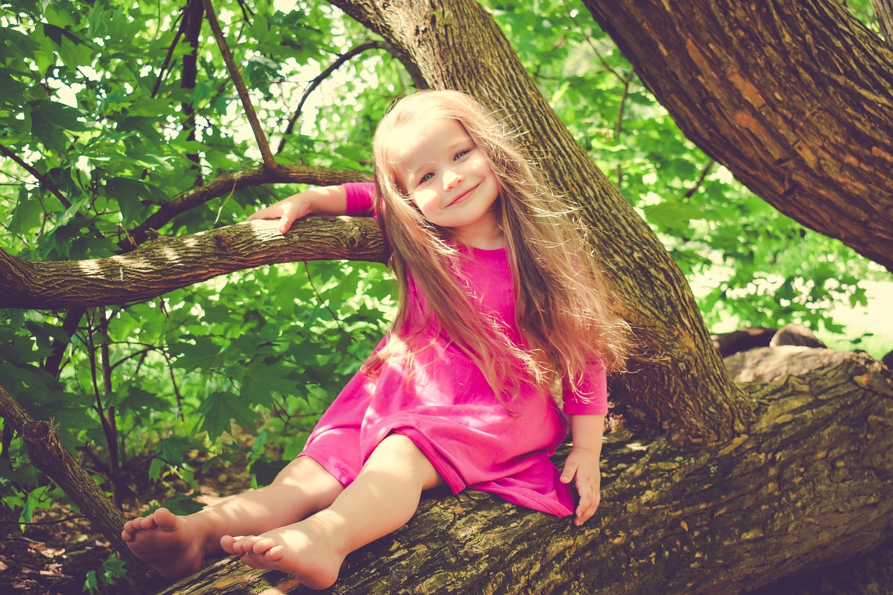 Smiling young girl in a pink dress in a tree